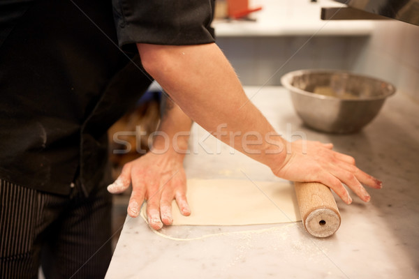 chef with rolling-pin rolling dough at kitchen Stock photo © dolgachov