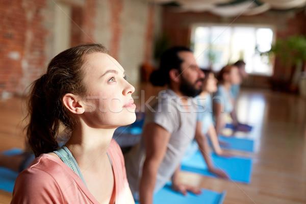 group of people doing yoga cobra pose at studio Stock photo © dolgachov