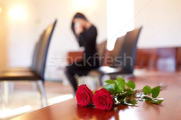 red roses and woman crying at funeral in church Stock photo © dolgachov