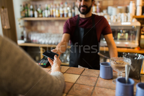 man with payment terminal and hand with smartphone Stock photo © dolgachov
