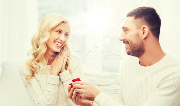 happy man giving engagement ring to woman at home Stock photo © dolgachov