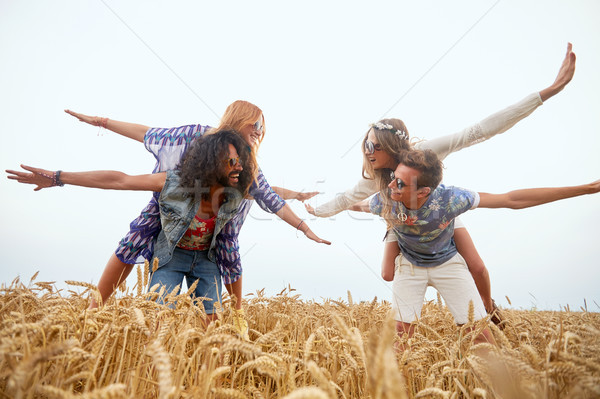 happy hippie friends having fun on cereal field Stock photo © dolgachov