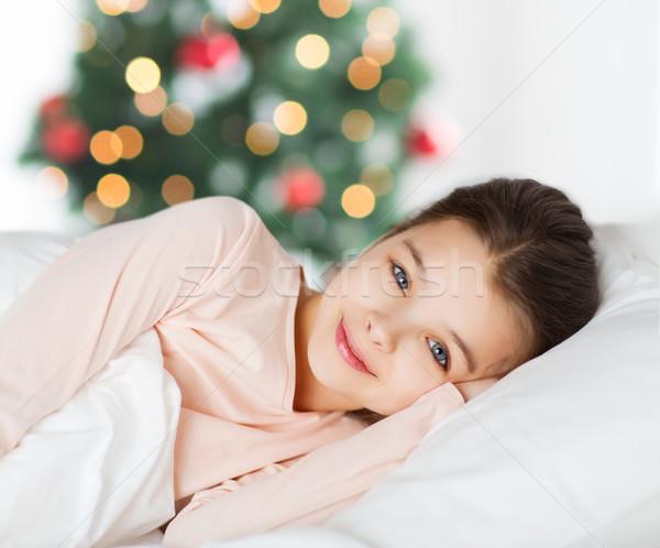 Feliz sorridente menina desperto cama natal Foto stock © dolgachov