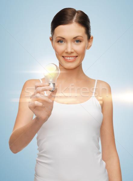 woman with energy saving bulb Stock photo © dolgachov