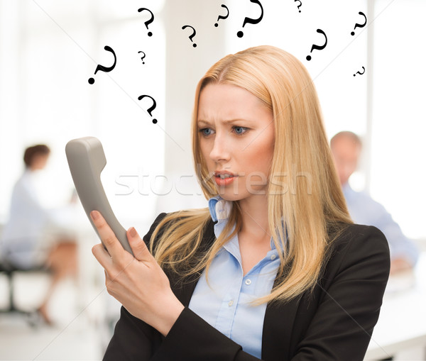 Stock photo: confused woman with phone in office