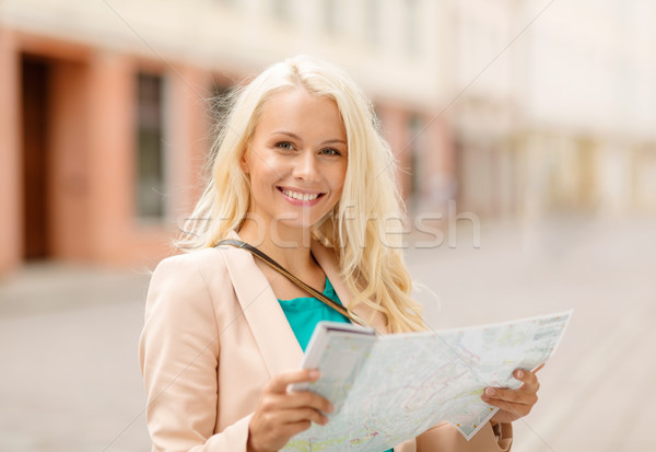 smiling girl with tourist map in the city Stock photo © dolgachov
