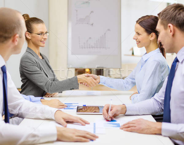two businesswomen shaking hands in office Stock photo © dolgachov