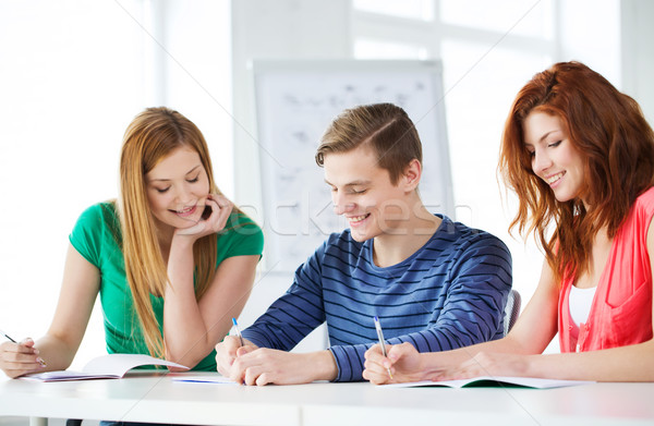 smiling students with textbooks at school Stock photo © dolgachov