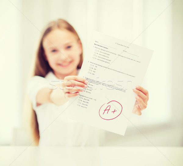 smiling little student girl with test and A grade Stock photo © dolgachov
