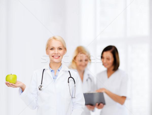 Glimlachend vrouwelijke arts groene appel gezondheidszorg Stockfoto © dolgachov