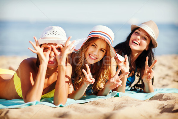 girls sunbathing on the beach Stock photo © dolgachov
