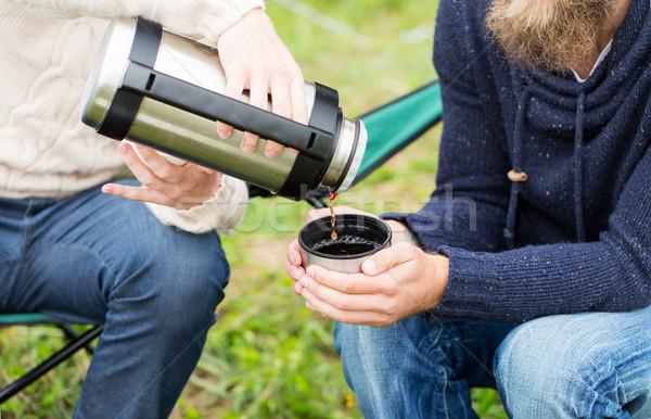 close up of hikers pouring tea from thermos to cup Stock photo © dolgachov