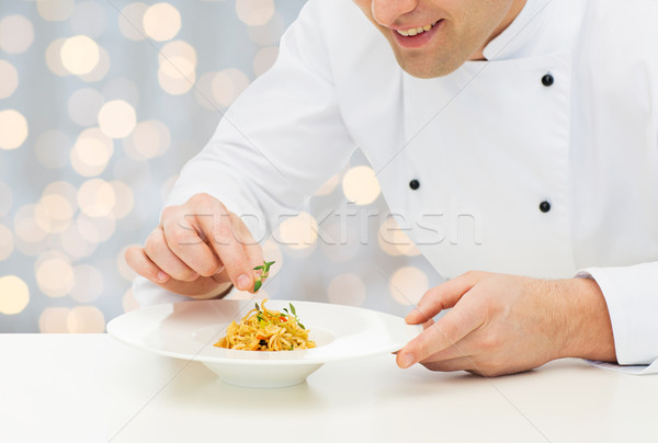 close up of happy male chef cook decorating dish Stock photo © dolgachov