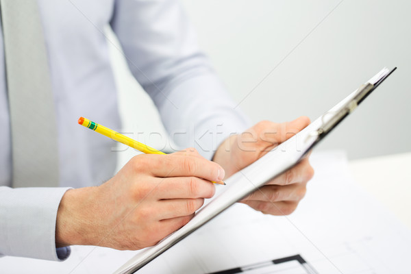 close up of businessman hands with clipboard Stock photo © dolgachov