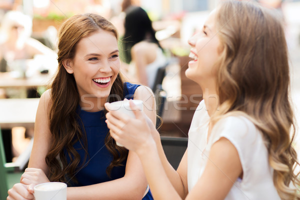 smiling young women with coffee cups at cafe Stock photo © dolgachov