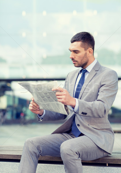 Stock photo: young serious businessman newspaper outdoors