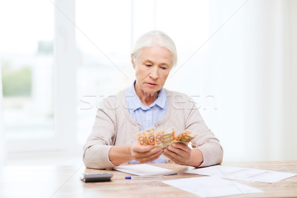 senior woman with money and papers at home Stock photo © dolgachov