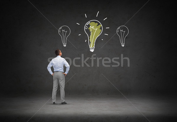businessman looking at lighting bulb doodles Stock photo © dolgachov