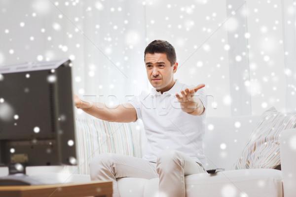 Deluso uomo guardare tv home persone Foto d'archivio © dolgachov