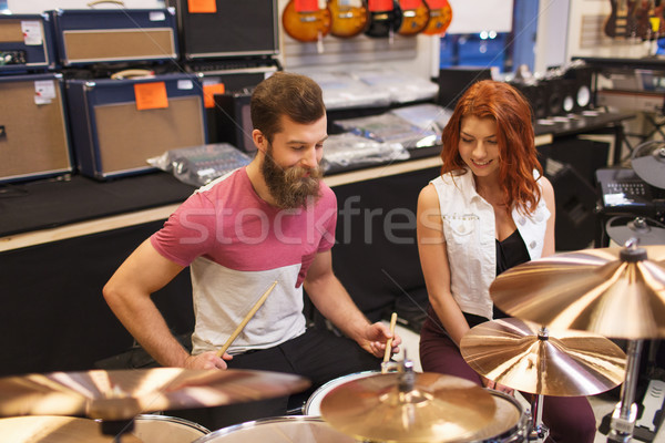 happy man and woman playing cymbals at music store Stock photo © dolgachov