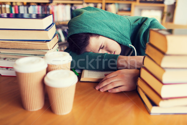 tired student or man with books in library Stock photo © dolgachov
