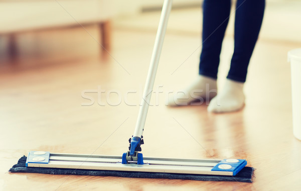 close up of woman with mop cleaning floor at home Stock photo © dolgachov