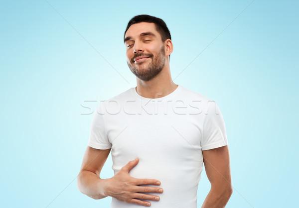 happy full man touching tummy over blue background Stock photo © dolgachov
