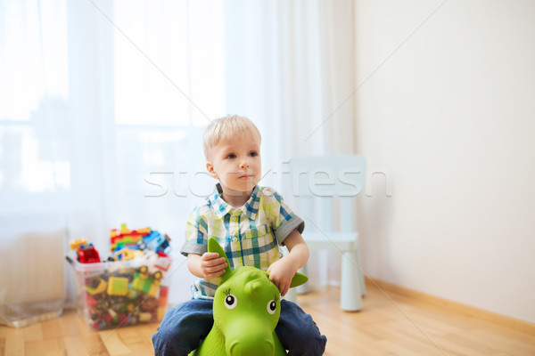 happy baby boy playing with ride-on toy at home Stock photo © dolgachov