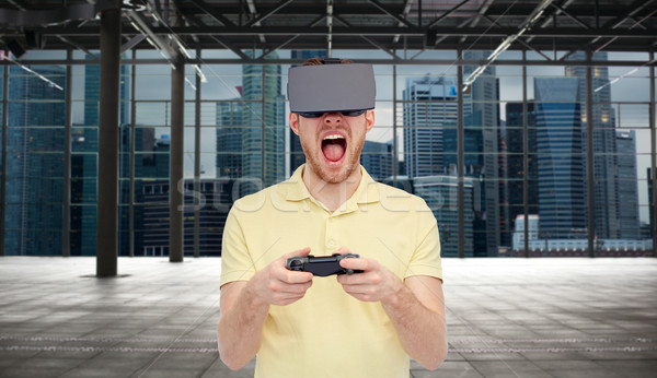 angry man in virtual reality headset with gamepad Stock photo © dolgachov