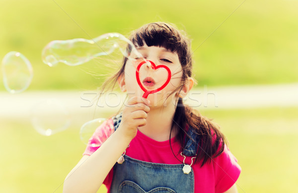 little girl blowing soap bubbles outdoors Stock photo © dolgachov