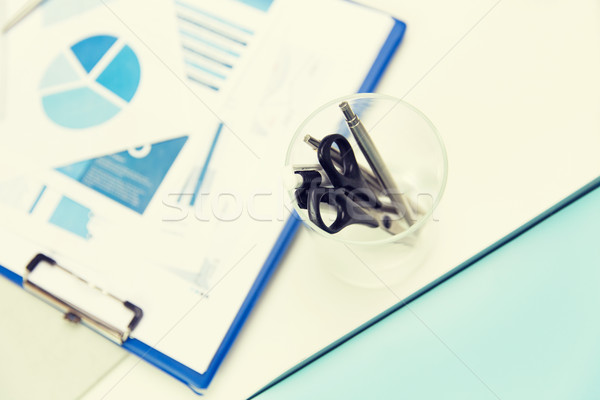 close up of cup with scissors and pens at office Stock photo © dolgachov