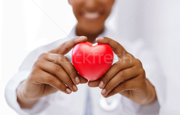 african female doctor with red heart Stock photo © dolgachov