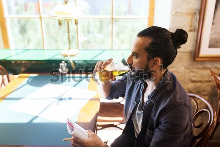 man with tablet pc drinking beer at bar or pub Stock photo © dolgachov