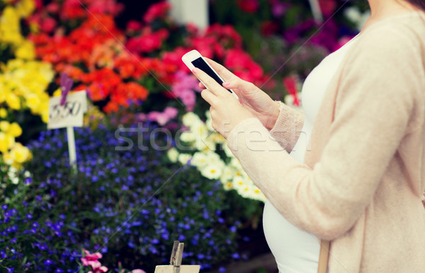 pregnant woman with smartphone at flower market Stock photo © dolgachov