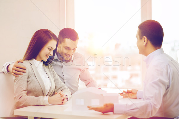 couple looking at model of their house at office Stock photo © dolgachov