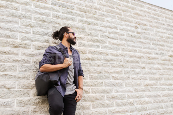 man with backpack standing at city street wall Stock photo © dolgachov