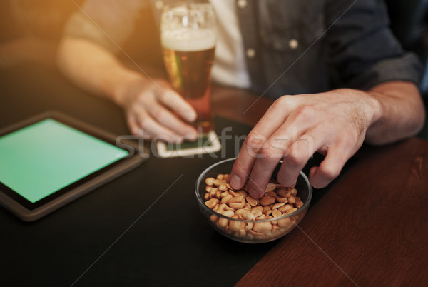 man with tablet pc, beer and peanuts at bar or pub Stock photo © dolgachov