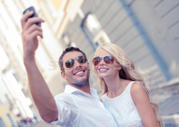 улыбаясь пару смартфон город лет праздников Сток-фото © dolgachov