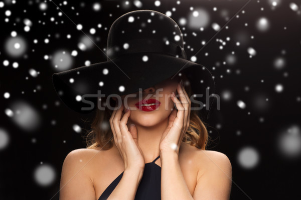 beautiful woman in black hat over snow Stock photo © dolgachov