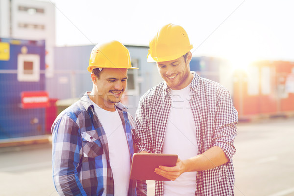 Stock photo: smiling builders in hardhats with tablet pc