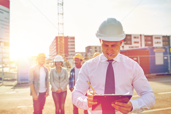 happy builders and architect at construction site Stock photo © dolgachov