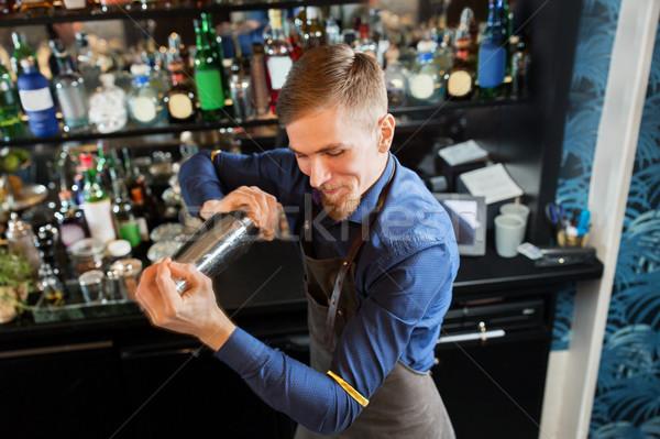 happy barman with shaker preparing cocktail at bar Stock photo © dolgachov