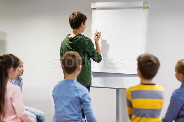student boy with marker writing on flip board Stock photo © dolgachov