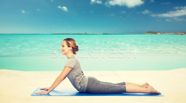 woman making yoga in dog pose on beach  Stock photo © dolgachov