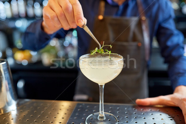 bartender decorating glass of cocktail at bar Stock photo © dolgachov
