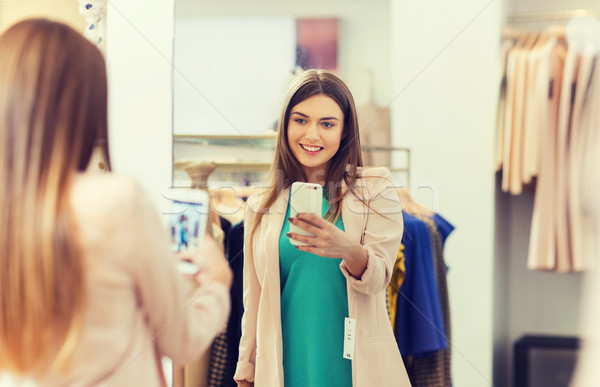 woman taking mirror selfie by smartphone at store Stock photo © dolgachov