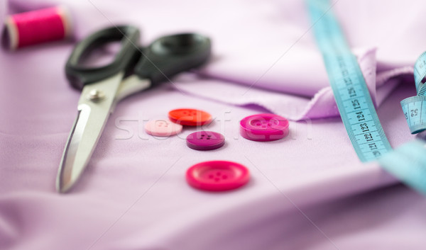 scissors, sewing buttons, tape measure and cloth Stock photo © dolgachov