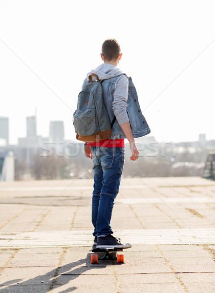 happy young man or teenage boy riding on longboard Stock photo © dolgachov