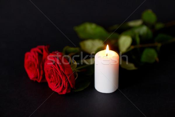 red roses and burning candle over black background Stock photo © dolgachov