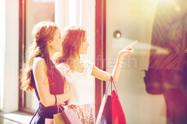 Boldog nők bevásárlótáskák bolt ablak vásár Stock fotó © dolgachov